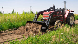 Compact tractor with front loader leveling ground